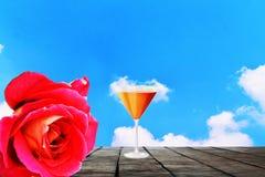 杯果汁和玫瑰在一张老木桌上 免版税库存照片