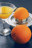 杯橙汁、剥削者和桔子在木背景 免版税库存照片