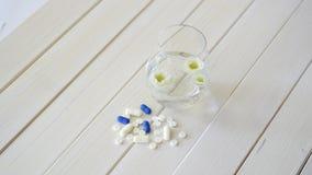 杯水晶水和套在白色木桌上的药片 影视素材