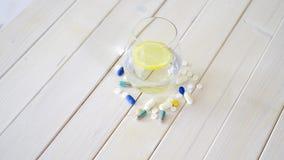 杯水晶水用柠檬和套在白色木桌上的药片 股票录像