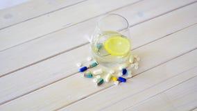杯水晶水用柠檬和套在白色木桌上的药片 股票视频