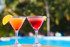 杯水果鸡尾酒和太阳镜由海滩 免版税库存照片