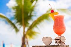 杯水果鸡尾酒和太阳镜由海滩 图库摄影
