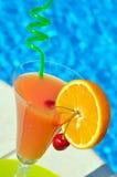 杯汁液和一棵樱桃在一块绿色板材 图库摄影