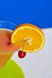 杯汁液和一棵樱桃在一块绿色板材 免版税库存照片