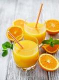 杯汁液和橙色果子 免版税库存图片