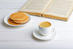 杯浓咖啡、奶蛋烘饼和书 免版税库存照片