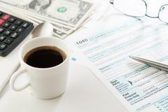 杯浓咖啡和收入税单形式与金钱、计算器和玻璃 库存图片