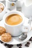 杯浓咖啡和曲奇饼在一张白色桌,垂直,特写镜头上 免版税库存图片