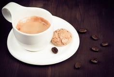 杯浓咖啡咖啡和饼干在咖啡豆附近,老牌 免版税库存照片