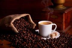 杯浓咖啡用在木桌上的咖啡豆 图库摄影