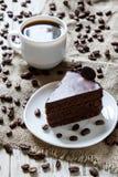 杯浓咖啡,在桌上的咖啡豆与麻袋布,巧克力蛋糕片断  免版税库存照片