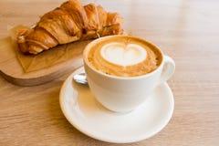 杯热奶咖啡和新月形面包 图库摄影