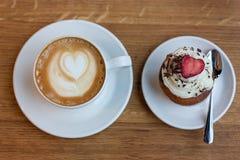 杯热奶咖啡和杯形蛋糕 免版税图库摄影