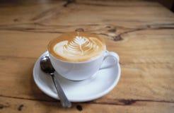 杯热奶咖啡在木纹理桌上 免版税库存照片