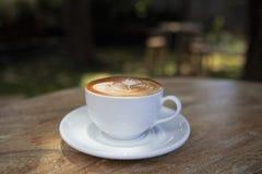 杯热奶咖啡在木纹理桌上 免版税库存图片