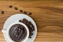 杯热巧克力和咖啡豆在一个木板 免版税库存照片