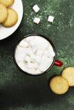杯热巧克力和曲奇饼圣诞节的在一绿色backgr 免版税库存照片
