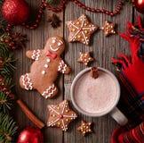 杯热巧克力或可可粉与姜饼人,温暖的围巾构成在杉树装饰 方形的看法 免版税库存照片