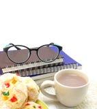 杯热巧克力用与一本书的牛奶在背景中 免版税库存图片