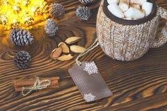 杯热巧克力用蛋白软糖、坚果和桂香葡萄酒木表面上与圣诞灯在背景, selecti 库存照片