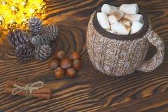 杯热巧克力用蛋白软糖、坚果和桂香葡萄酒木表面上与圣诞灯在背景, selecti 免版税库存图片