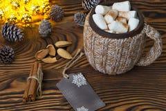 杯热巧克力用蛋白软糖、坚果和桂香葡萄酒木表面上与圣诞灯在背景 库存图片
