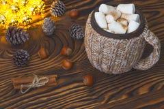 杯热巧克力用蛋白软糖、坚果和桂香葡萄酒木表面上与圣诞灯在背景 免版税库存照片