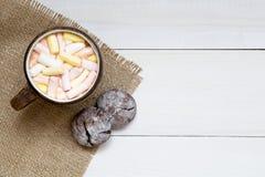 杯热的可可粉用蛋白软糖和曲奇饼在白色桌,顶视图,拷贝空间上 免版税库存图片
