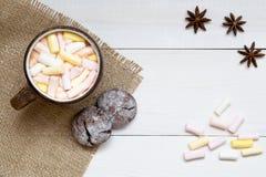 杯热的可可粉用蛋白软糖和曲奇饼在白色桌,顶视图,拷贝空间上 库存图片