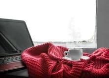 杯热的咖啡和一台膝上型计算机工作的 库存图片