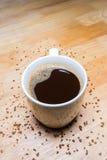 杯热的咖啡和咖啡粒子在木桌上 免版税库存照片