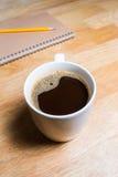 杯热的咖啡和笔记本在木桌上 库存照片