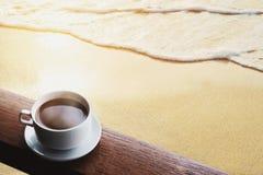 杯热的咖啡在木桌上喝,在日出的海滩 免版税库存图片