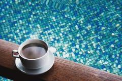 杯热的咖啡在木桌上在游泳池背景中喝,用水 图库摄影