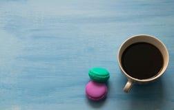 杯热的咖啡用在蓝色背景的蛋白杏仁饼干 免版税图库摄影