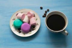 杯热的咖啡用蛋白软糖和蛋白杏仁饼干在蓝色背景 库存图片