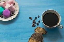杯热的咖啡用蛋白软糖和蛋白杏仁饼干在蓝色背景 免版税库存照片