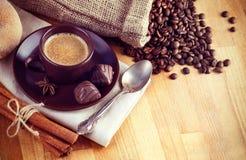杯热的咖啡用豆和巧克力糖 免版税库存图片