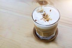 杯热的咖啡饮料用在上面的花生在木桌上 库存照片