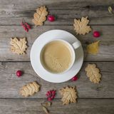 杯热的咖啡,在形式叶子、干燥秋叶、山楂树和伏牛花果子的曲奇饼在木背景 顶视图,平 库存图片