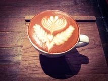 杯热的拿铁或热奶咖啡与引人入胜的拿铁艺术 库存照片