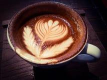 杯热的拿铁或热奶咖啡与引人入胜的拿铁艺术 库存图片