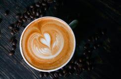 杯热的拿铁或热奶咖啡与引人入胜的拿铁艺术 免版税库存照片