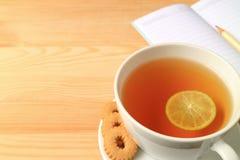 杯热的柠檬茶用曲奇饼和被排行的便条纸在木表上,与自由空间 图库摄影