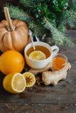 杯热的柠檬茶用橙色南瓜和姜在木背景阻塞 健康饮料寒冷 冬天饮料 图库摄影