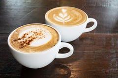 杯热的热奶咖啡和拿铁艺术咖啡 库存照片