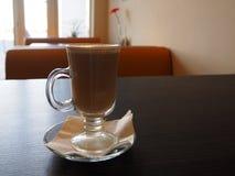 杯热的热奶咖啡用桂香和在木桌上的白色泡沫 免版税图库摄影