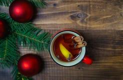杯热的芳香茶用肉桂条和柠檬与圣诞树分支和红色球在木桌背景 免版税库存照片