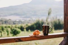 杯热的茶和新月形面包在阳台有后边山的 免版税图库摄影